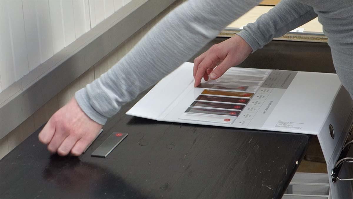 Einschieben der Farbmusterlaschen in den Produktkatalog ISN